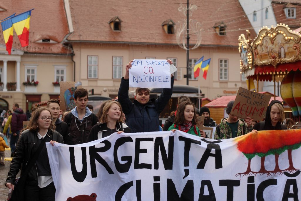 An image of climate strikers marching through a Christmas Market with a banner.