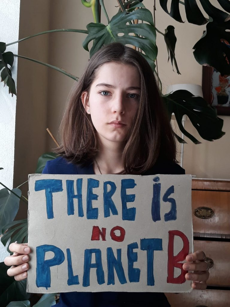 Paula holding a sign reading there is no planet B, as part of the 2020 digital strike.