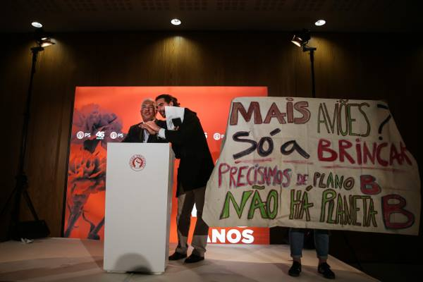 Kiko, a climate activist, interupts the Portuguese President speaking on a podium, a banner is held next to them by a further activist, with Portuguese text opposing the airport