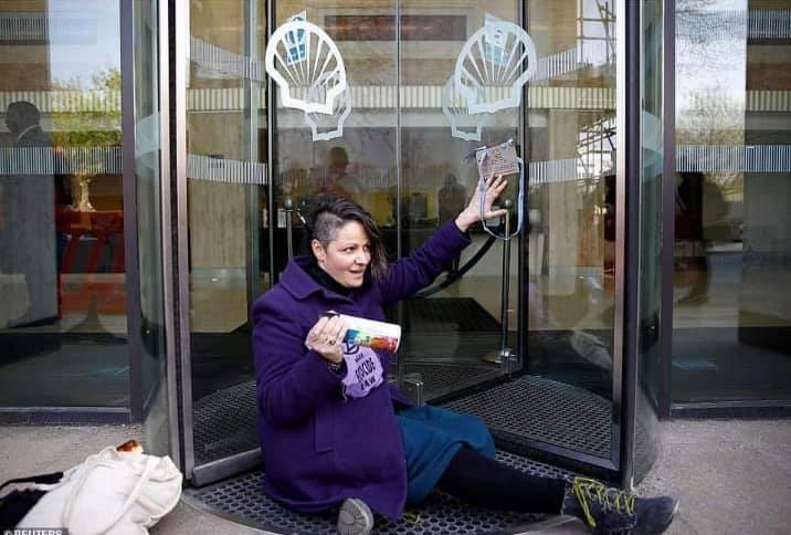 An activists sits blocking the entrance to Shell's headquarters, glued to the glass revolving door.