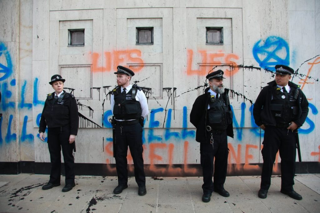 Four police officers stand in front of the Shell headquarters, graffiti covers the walls behind them.