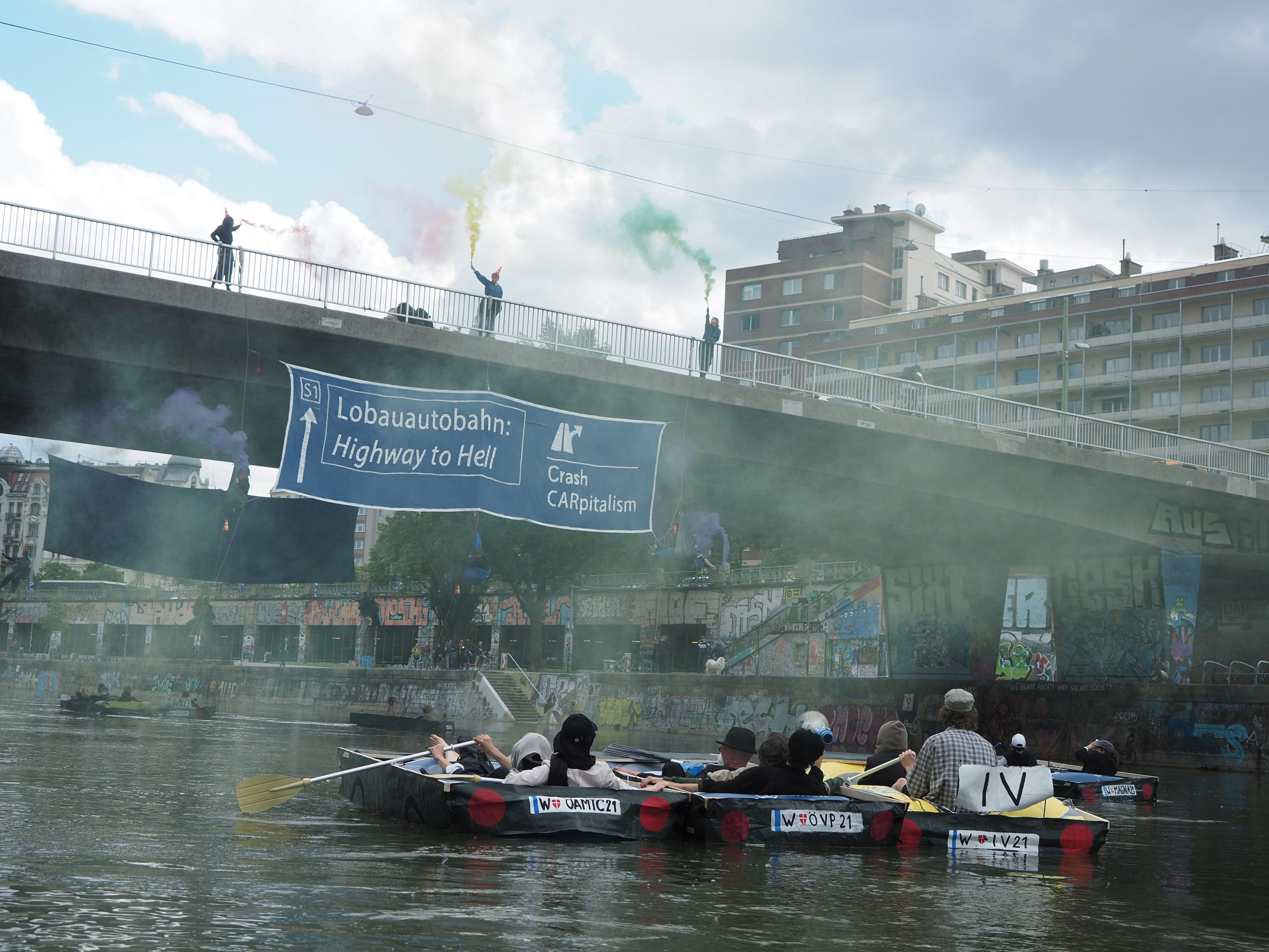 Activists in boats made to look like cars float in the Danube Canal, looking up at activists occupying the Aspern bridge with smoke.